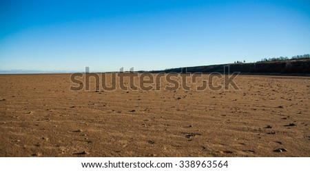 The wide sandy beach of the lake and a flat horizon - stock photo
