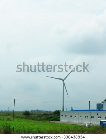 the wind-driven generator in the middle of a field serves for development of the cheap and ecology electric power