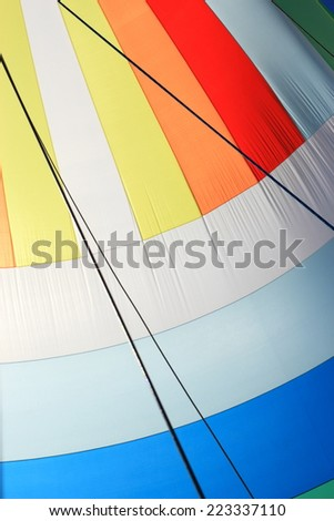 The wind has filled the spinnaker on sailing yacht. Detail of a colorful sail as background.