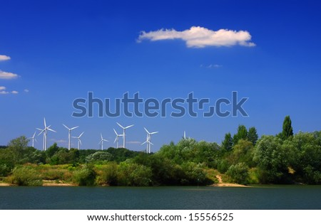 The windmills among trees after second side of lake