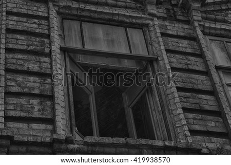 The window of the old creepy abandoned scary house in which lives a Ghost and a murder (black-and-white photo) - stock photo