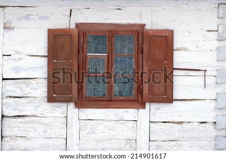 The window of the old wooden log house on the background of wooden walls