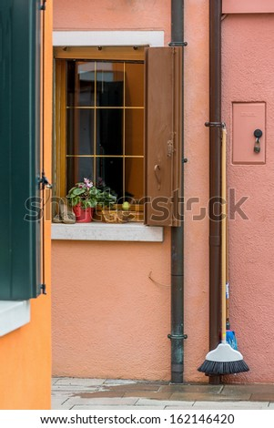 The window with flower on the ancient wall of the house - Burano, Venice, Italy