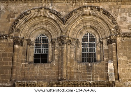 The windows above the entrance to the Church of the Holy Sepulchre in the old city of Jerusalem. Just below the right window, the famous ladder of the status quo is seen (it's been there since 1854). - stock photo