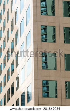 The windows of a metropolitan high rise reflect bright summer sun in the city. - stock photo
