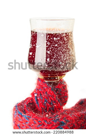 The Wineglass with Wine Muffled in Scarf and Covered with Snow - stock photo