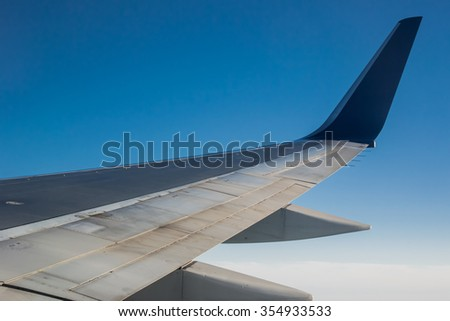 The wing of an airplane against a blue sky