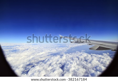 the wing of an airplane flying above the clouds - airplane transportation icon