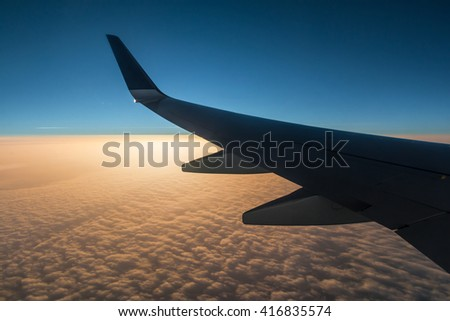 The wing of the airplane above the clouds at sunset - stock photo