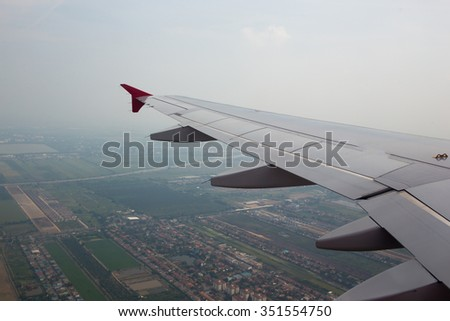 The wings of the plane, and the beautiful view from the glass window of the plane
