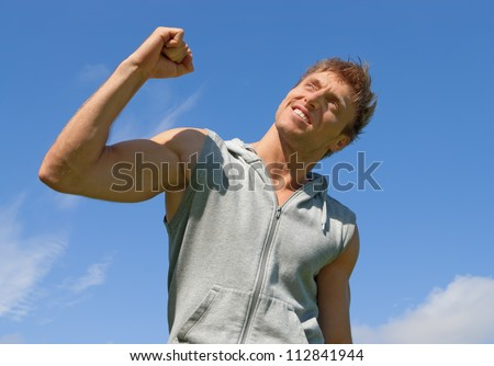 The winner. Energetic young man with his arm raised in joy. - stock photo