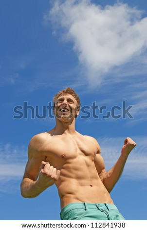 The winner. Fit smiling guy showing his strength. - stock photo