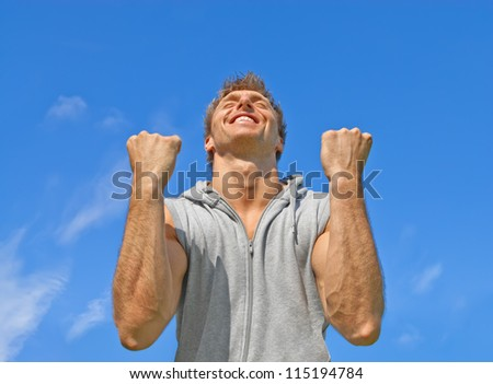 The winner. Happy energetic young man on blue sky background. - stock photo