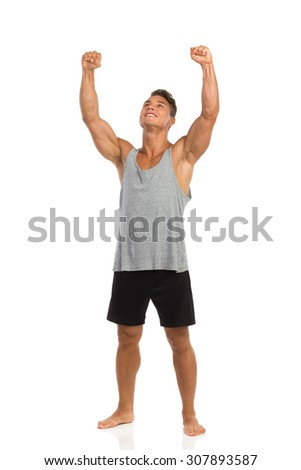The winner. Happy muscular man standing barefoot, holding arms raised and looking up. Full length studio shot isolated on white.