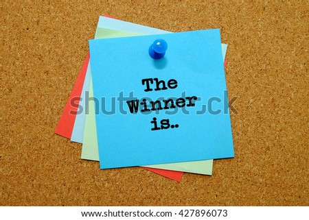 The winner is written on colored sticker notes over cork board background.