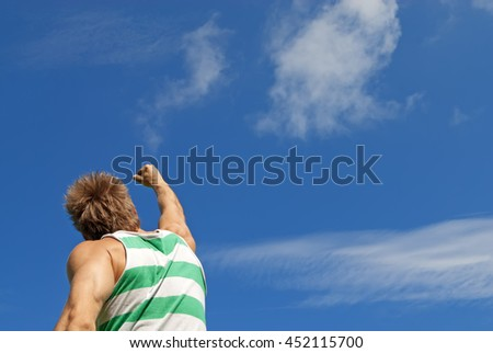 The winner. Sporty guy with his arm raised in joy, on blue sky background.