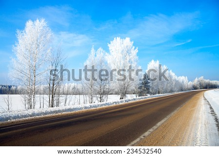 the winter rural  landscape with the road the forest and the blue sky - stock photo