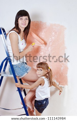 The woman and the child paint the wall on the ladder
