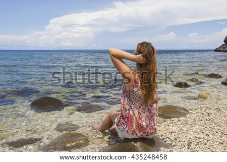 The woman and the sea, young red hair woman sitting by the sea on the beach, staring at sea picture, meditation by sea image, ecotourism illustration: clear water and sand empty beach, loose hair girl - stock photo