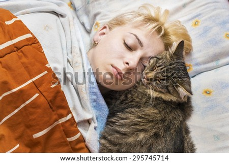 The woman asleep in bed with a striped cat - stock photo