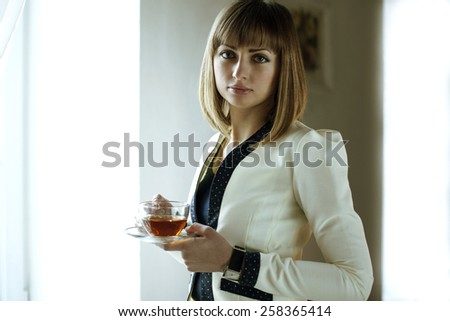 The woman at the window with a cup of tea. Woman - office worker drinking tea. Break for tea. Office style women. Cup of tea in her hands. - stock photo