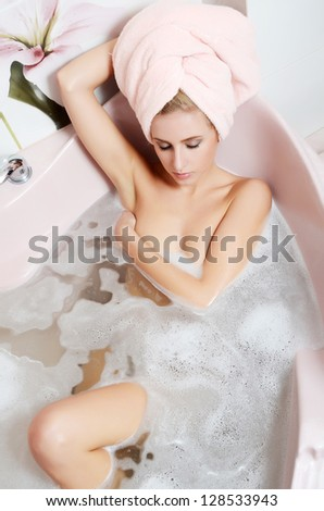 The woman blonde in bath  with foam