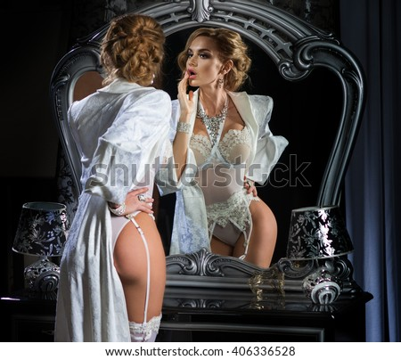 The woman corrects make-up, standing in front of a mirror in an expensive, white lingerie and long robe - stock photo