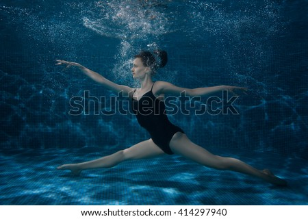 The woman dances at the bottom under water, she is surrounded by bubbles.