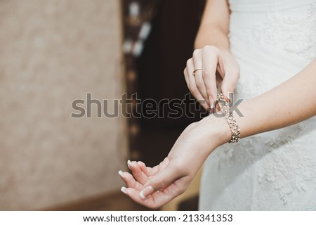 The woman dresses on a hand a bracelet and clasps it.