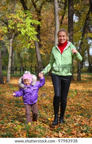 The woman flees with her daughter in the autumn park
