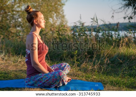 The woman girl is doing yoga exercises on the river bank