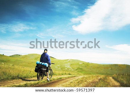 The woman going on a bicycle against mountains - stock photo
