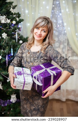 The woman holds a gift at the Christmas tree in home interior
