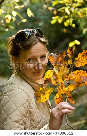 The woman holds in a hand a branch with yellow leaves