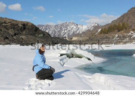 The woman in a blue jacket looking at the thawing river among mountains in the spring, Russia, Altai, Katun River, - stock photo