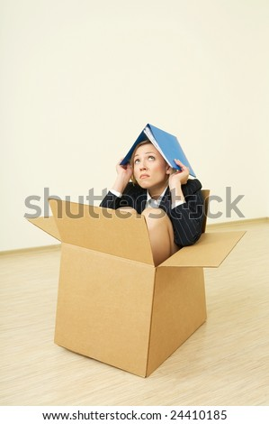 The woman in a business suit sitting in a cardboard box - stock photo