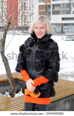 The woman in a fur coat and without cap in the winter.