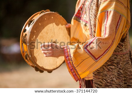 The woman in a national suit. Hand of the woman and tambourine. Playing a tambourine. - stock photo