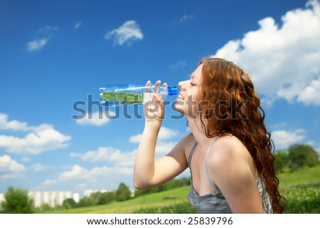 The woman in a profile drinks water from a bottle in park - stock photo
