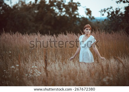 the woman in a white dress stays in the field. - stock photo