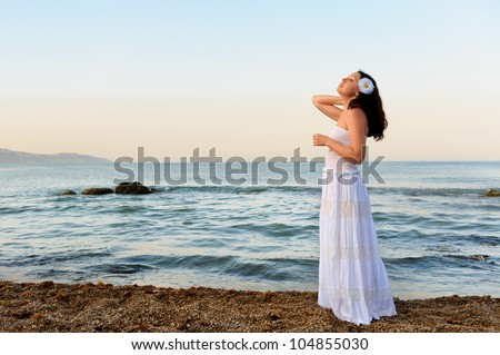 The woman in a white sundress on seacoast. A picturesque landscape