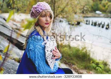 The woman in autumn knitted clothes poses on the island, an autumn depression