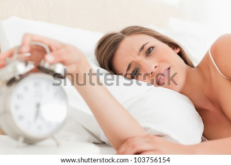 The woman in bed is looking straight ahead as she silences the alarm clock with her hand - stock photo