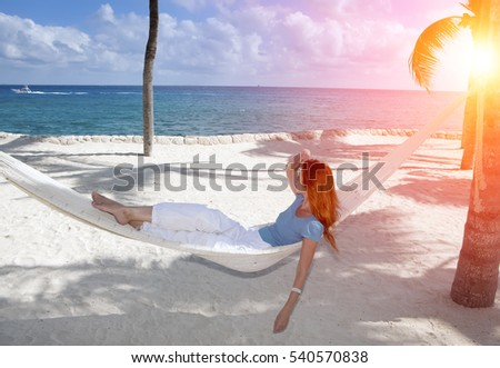 The woman in the hammock on background a blue sea