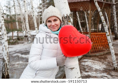 The woman in the middle of trees keeps in warm clothes naduveny the balloon in the form of heart