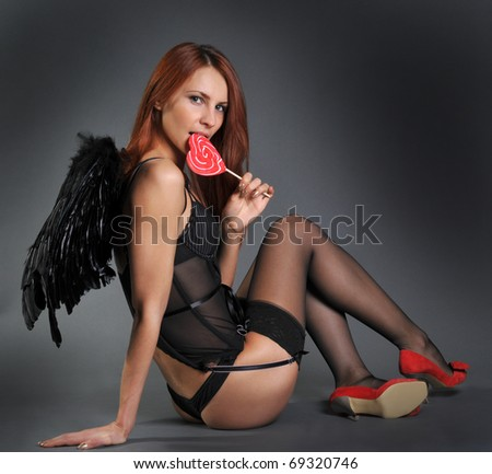 The woman in underwear in a suit of an angel with a sugar candy on a stick in the form of a heart - stock photo