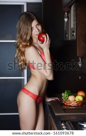 The woman in underwear with a basket of fruit on kitchen - stock photo