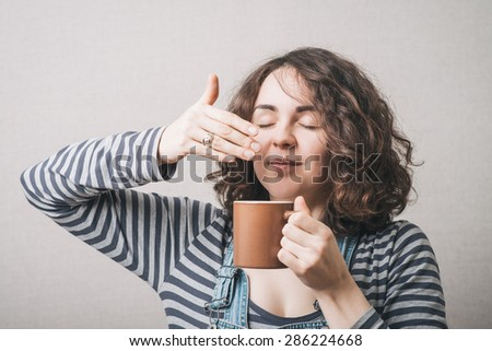 The woman inhales the smell of a cup of coffee or tea. Gray background - stock photo