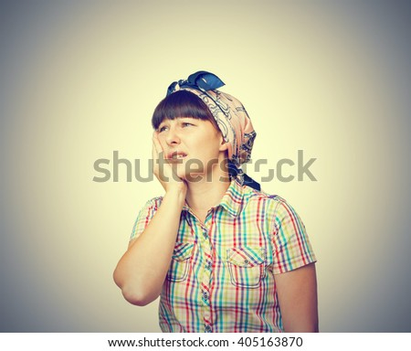 The woman is a housewife in a headscarf is suffering from a toothache isolated on gray background. - stock photo