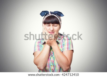 The woman is a housewife in a headscarf is suffering from a toothache isolated on gray background.
